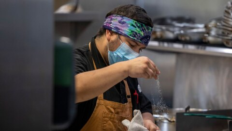 A cook at Eastvale Cafe prepares food in a kitchen.