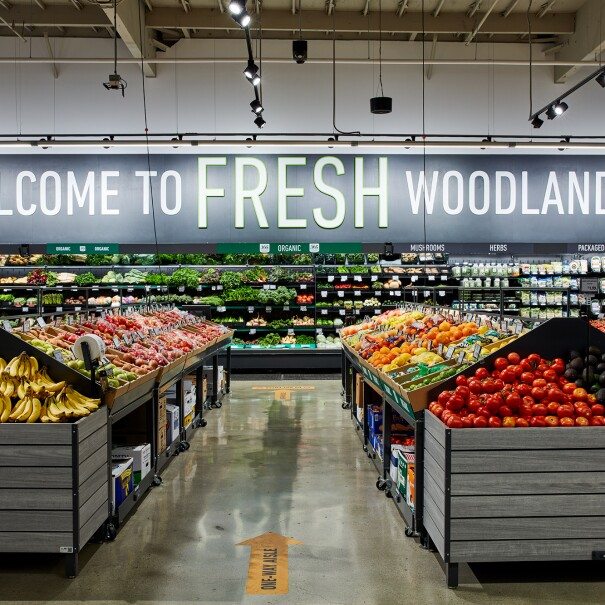 "Produce section of a grocery store with the words ""WELCOME TO FRESH WOODLAND HILLS"" on the back wall."