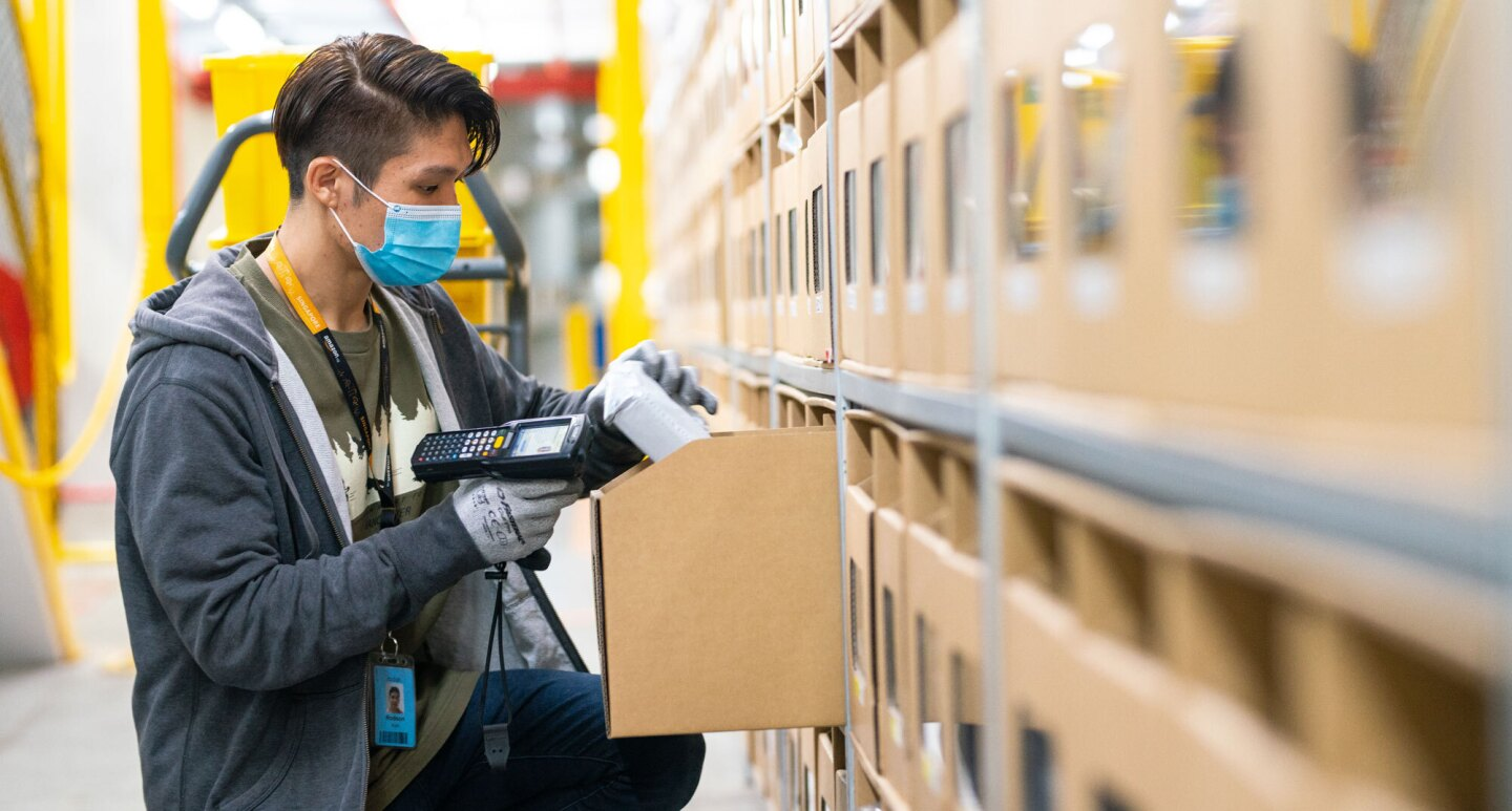 An Amazon employee wearing a face mask scans an item in a fulfilment centre.