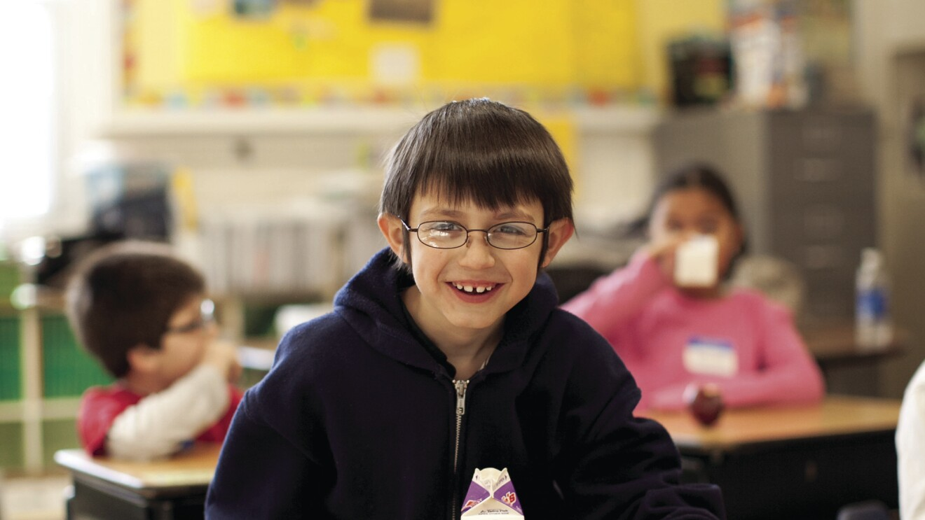 A boy sits at a school desk, smiling at the camera. On his desk are a carton of milk and a breakfast sandwich. Behind him, other students also eat and drink.
