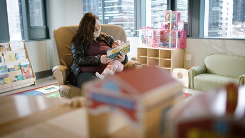 An image of a woman holding a baby on her lap while she reads her a story. They are sitting in a room with large windows, book shelves, and comfy chairs.