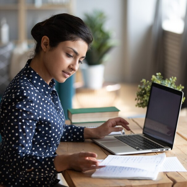 A woman wearing a polka-dotted blouse studies at her desk with her laptop and notes in front of her.