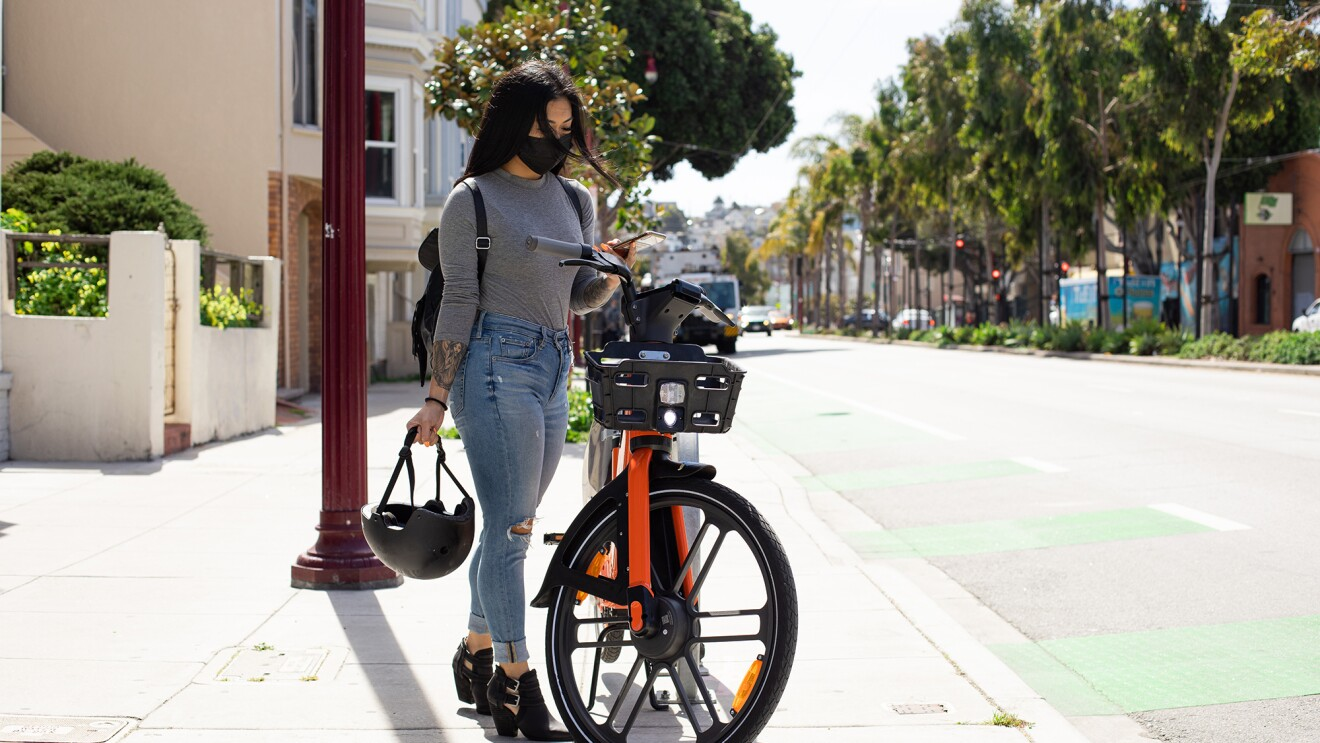 A woman scans a Spin bike with her mobile phone, in order to ride the bike in her city. She is wearing a mask and backpack, and holding a bike helmet.