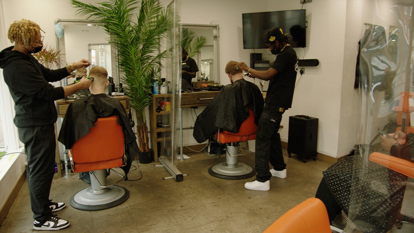 An image of two men cutting their clients' hair in a barber shop.