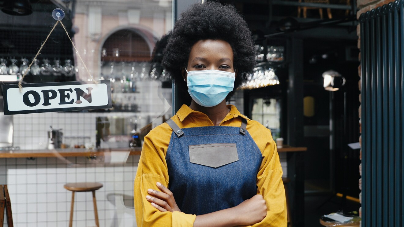 A Black woman wearing a mask and a denim apron stands in the open doorway of a restaurant