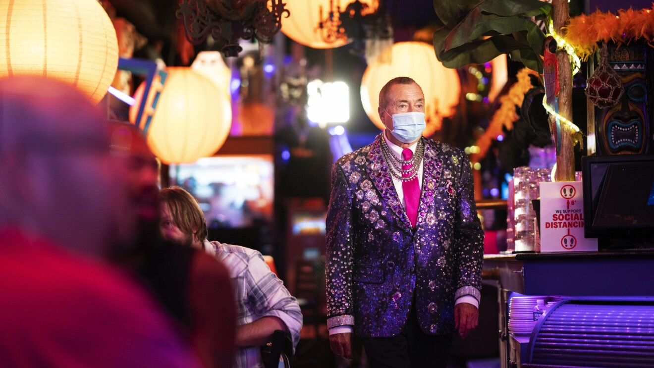 A man in a decorated purple blazer moves through a restaurant.