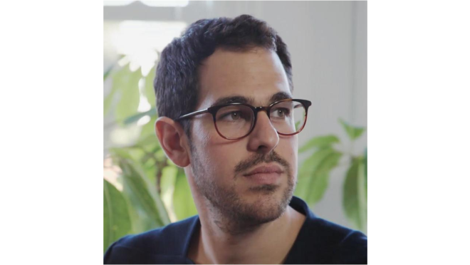 Ezequiel Karpf looks off into the distance and wears eyeglasses. There are houseplants behind him.