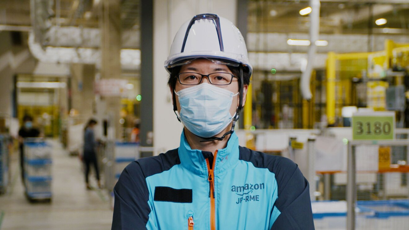 A person wearing a helmet and a face mask stands in an Amazon operations center and looks at the camera.
