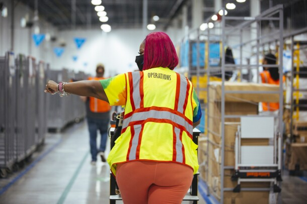 Wearing a yellow Operations safety vest, Auhzha Wright walks away from the camera and down an aisle at Amazon's Fulfillment center with her left arm extended and pointing out of frame.