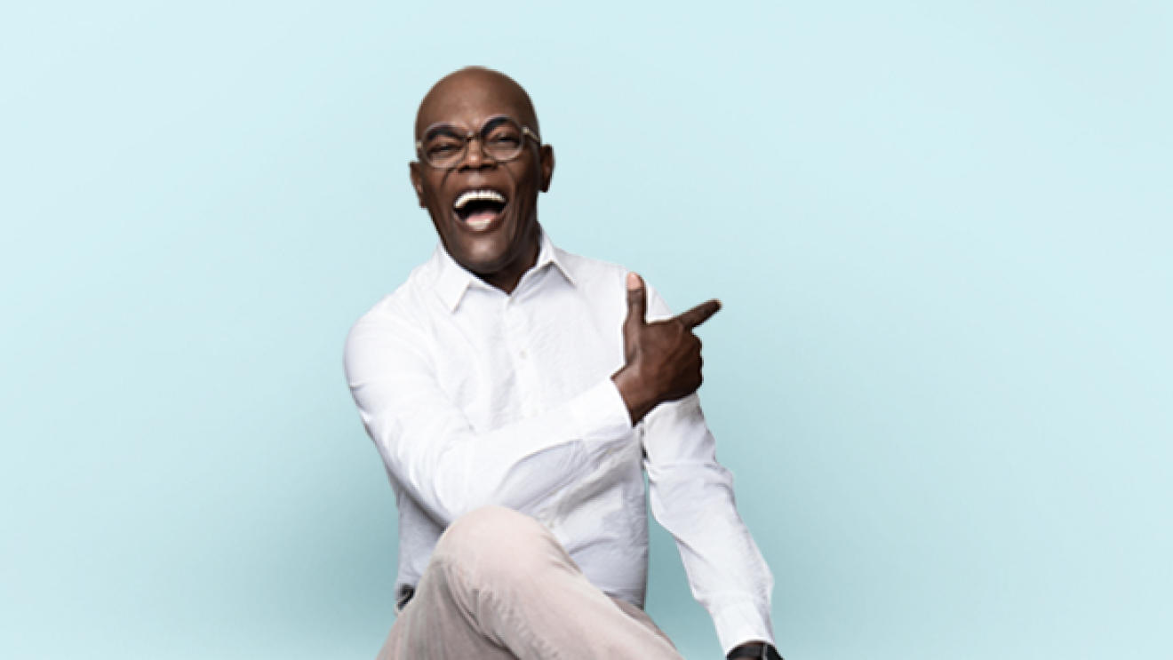 Samuel L. Jackson is laughing, sitting on a stool, and posing for a photo.