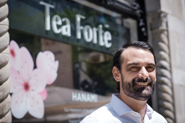 "A man stands in front of a storefront bearing a sign that says ""Tea FortŽé."""