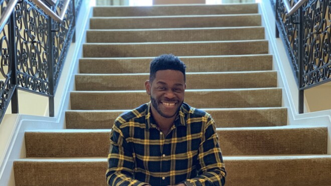 A man sits on a long staircase, while he smiles at the camera.