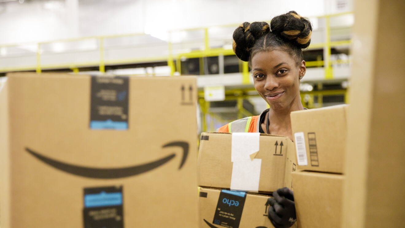 A smiling Amazon sortation associate in our Baltimore, Maryland sortation center looks at the camera from behind a pile of Amazon delivery boxes.