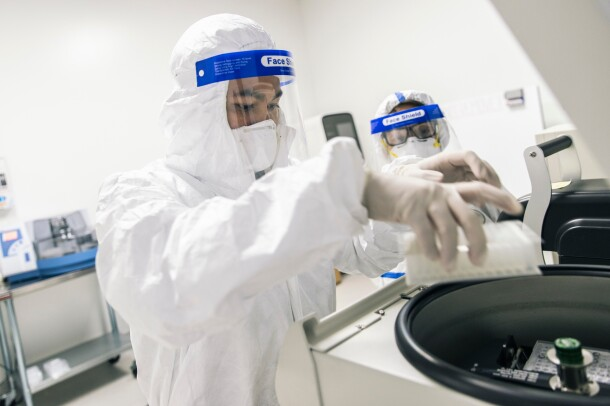 Two people in PPE. The person in the foreground places a tray inside a piece lab equipment.
