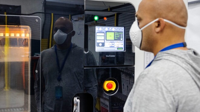 Mahale wears a face mask and stands in front of a 3D printer.