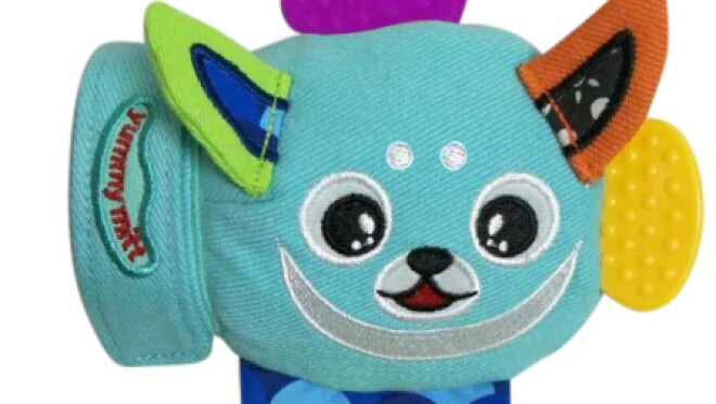 """A baby's mitten with various teething toys attached to it. The words """"yummy mitt"""" are on the wrist area of the mitten."""