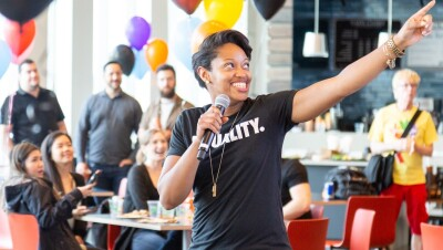 "A Black woman wearing a shirt that says ""Equality"" speaks into a microphone while gesturing off camera. She's speaking to a brightly decorated room full of people."