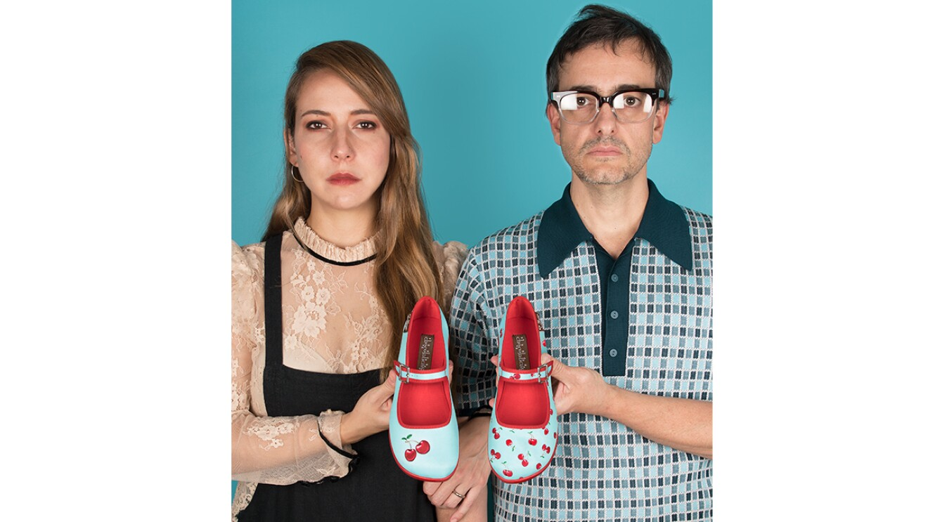 An image of a man and a woman standing in front of a teal background for a photo. They are each holding on shoe in a pair of colorful Mary Jane sandals. The shoes are light blue/teal with red inlining and red cherries on them. Both shoes look slightly different from one another.