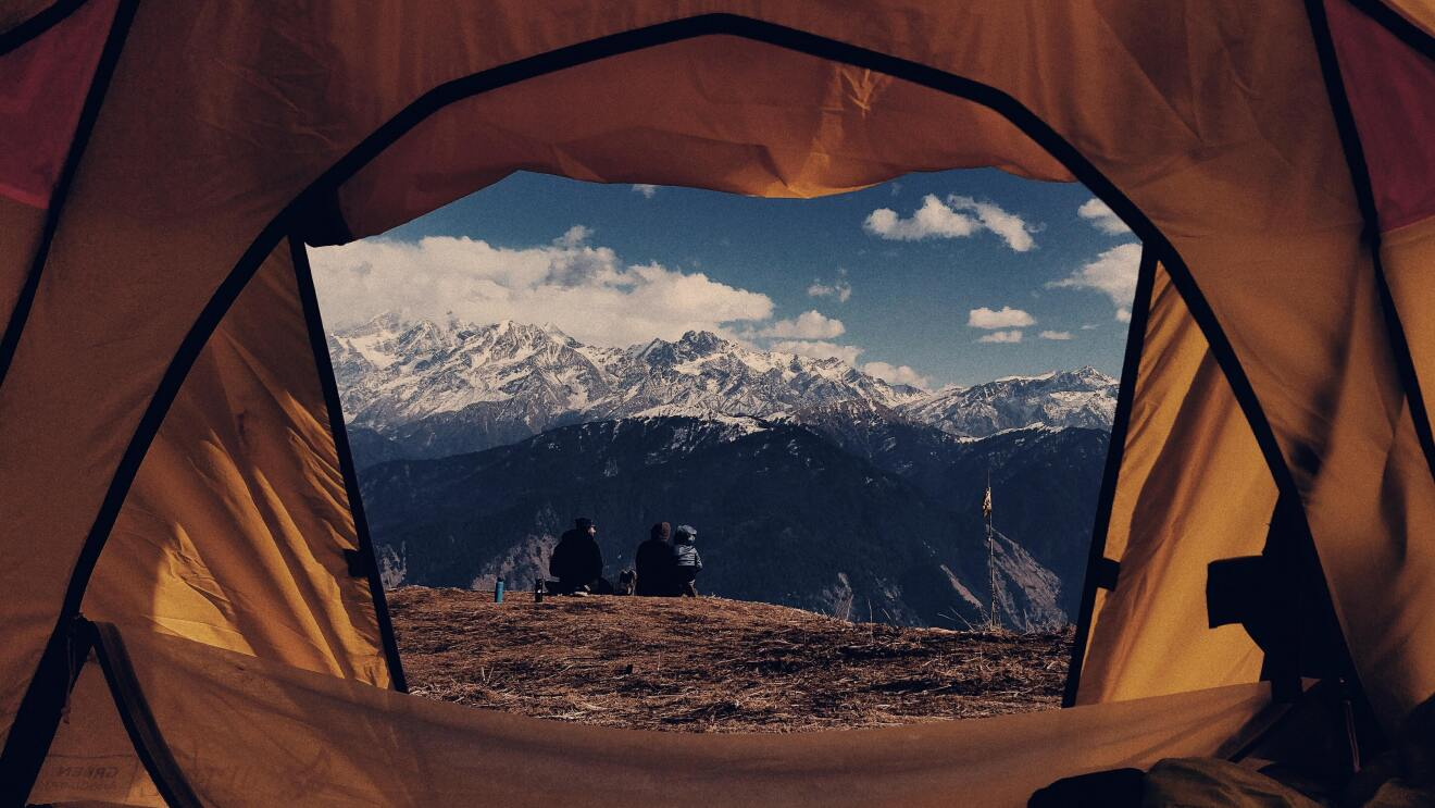A views from a camp tent shows 2 trekkers relaxing