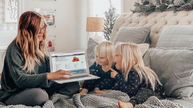 A women sits with her children showing them something on her laptop.