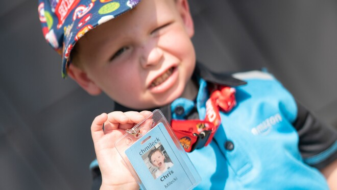 """An image of a boy with a colorful hat on that says """"hero"""" smiling for a photo while showing an Amazon badge with his name on it and wearing an Amazon shirt."""