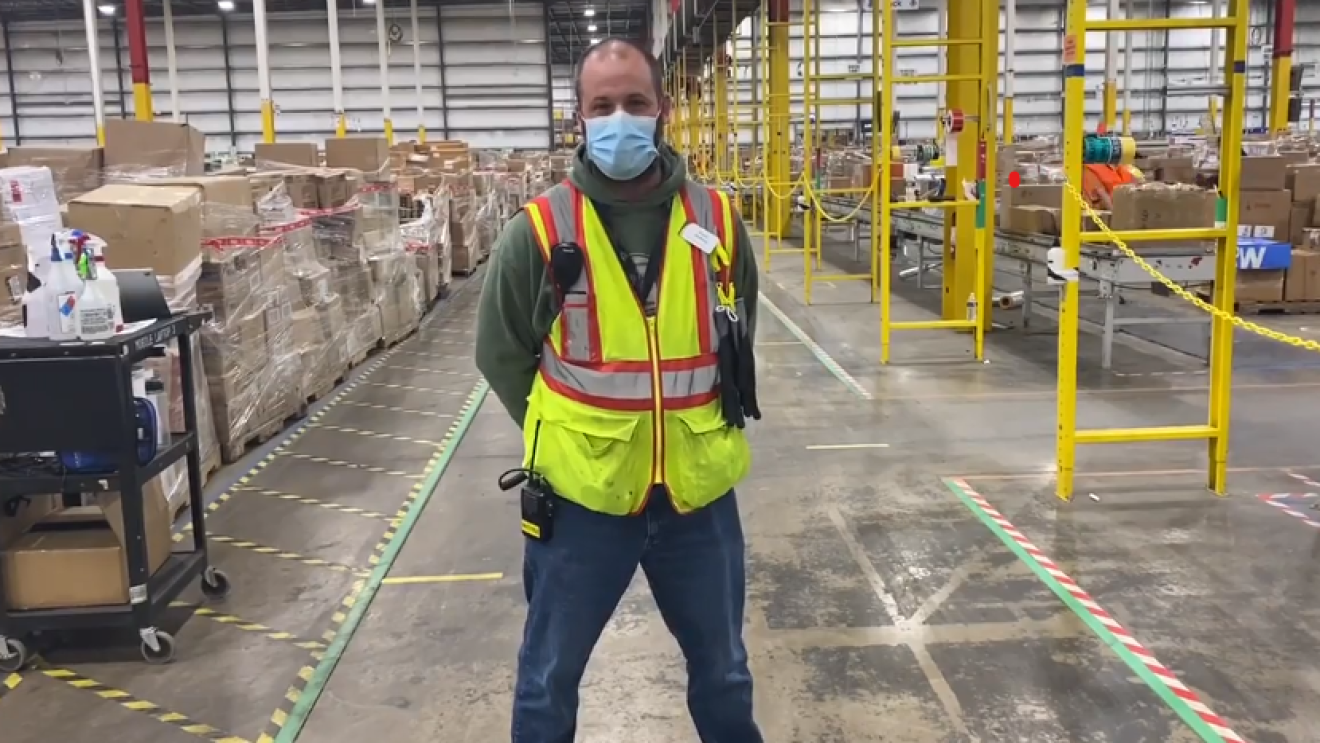 Russel Whitfield, an associate at Amazon, stands in an Amazon warehouse smiling for a photo. He is wearing a face mask and other Amazon warehouse safety gear.