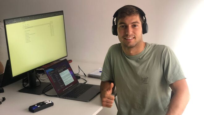 """An image of a man smiling for a photo at his computer while giving a """"thumbs up."""""""