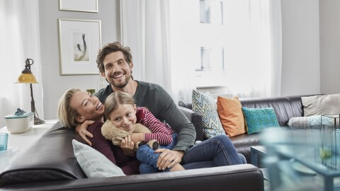 A family of three (mom, dad, child) is seated on a sofa in a contemporary living room.