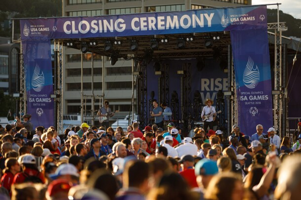 """The 2018 Special Olympics USA Games closing ceremony stage. Seattle band """"Hey Marseilles"""" performs (in the photo, a singer, bass player, keyboardist and electric guitarist), with a crowd of individuals in front of the stage."""