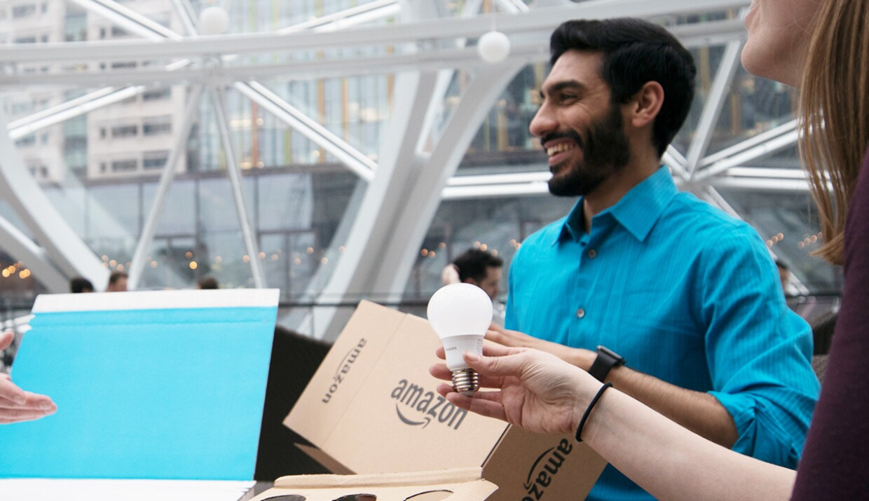 Three Amazon employees discuss the packaging of a light bulb.