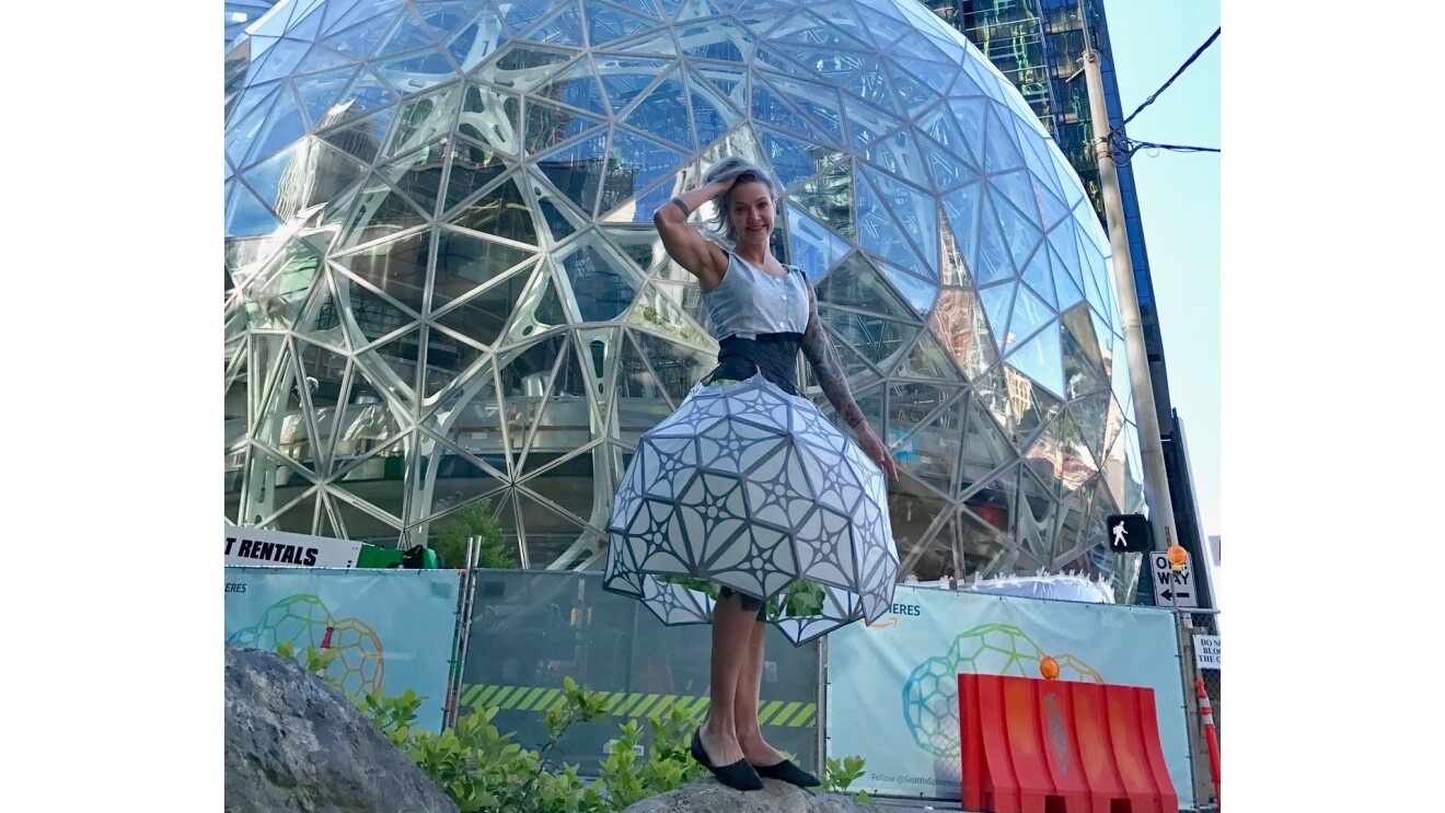 sheridan wearing a spherical dress and posing in front of the matching Amazon Spheres.