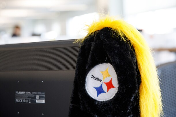 A black and yellow Pittsburgh Steelers cap hangs on the side of a computer monitor.