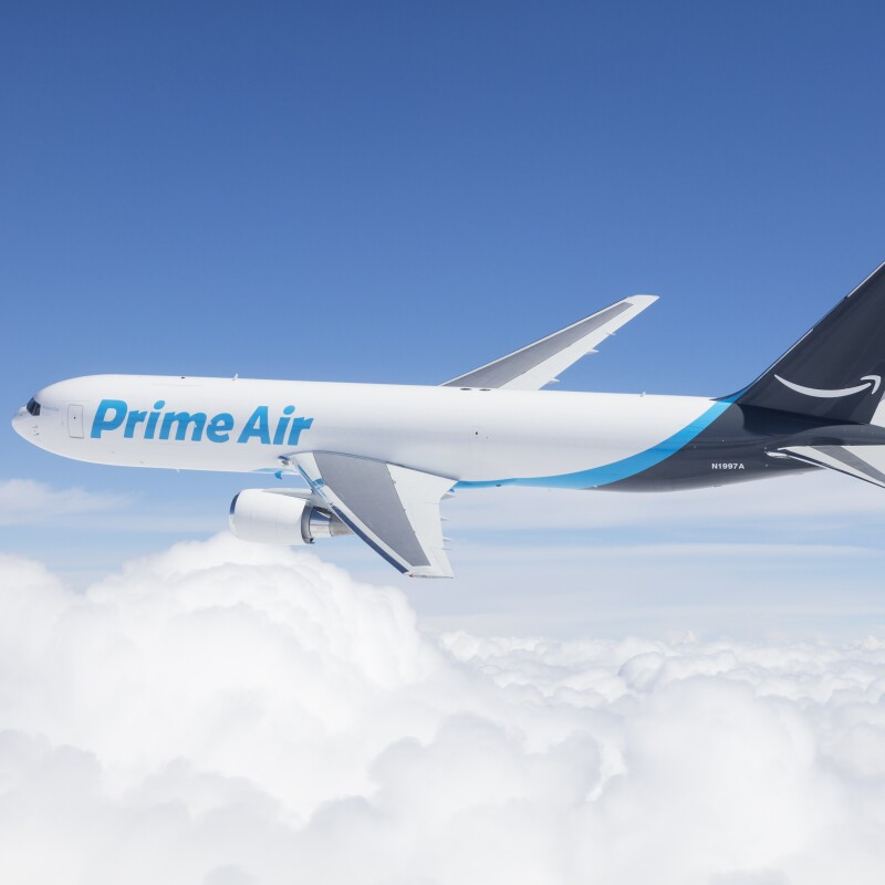 An Amazon Prime Air Boeing 767 flies above the clouds.