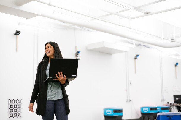 A woman stands in a white room, holding her laptop computer. Behind her, several Scout delivery robots are seen near the wall.