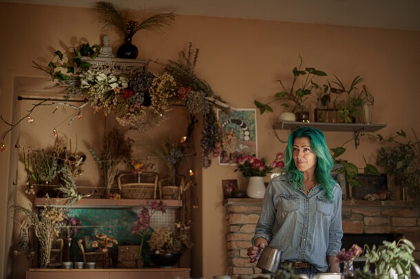 A woman wearing denim clothes stands in a room decorated with dried and living plants.