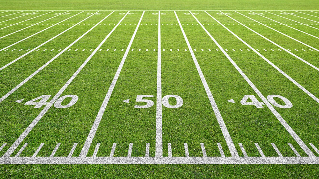 A sideline angle of yard lines are painted on a football field, centered on the 50-yard line.