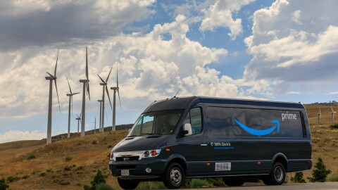 """An Amazon van with """"Prime,"""" the Amazon Smile, and """"100% electric"""" displayed on the side. The van is parked in front of several wind turbines."""