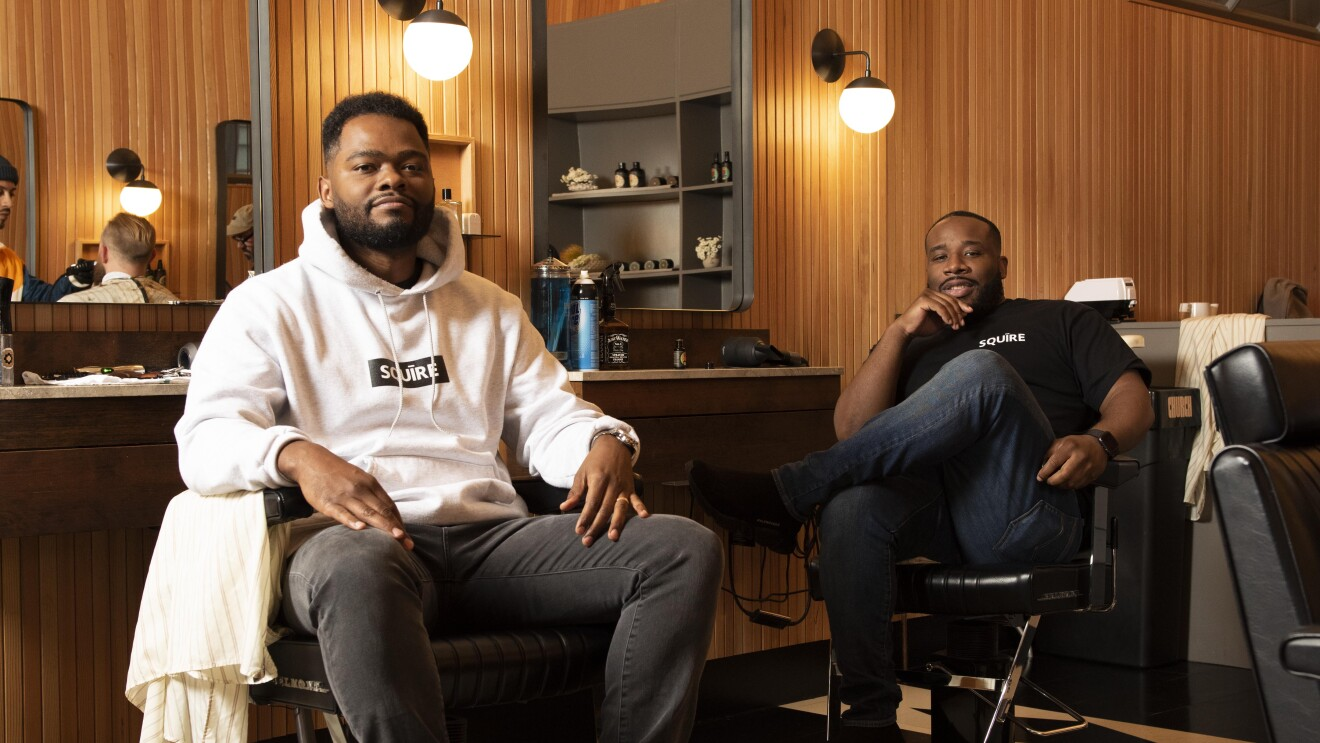 Two Black men, founders of the app Squire, sit in barber chairs in a barbershop setting.