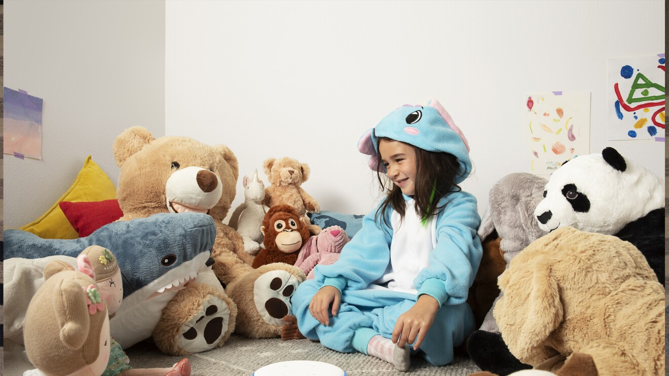 A child sits in a playroom, surrounded by stuffed animals. In front of her is an Echo Dot device is a rainbow stripe, on a tabletop.