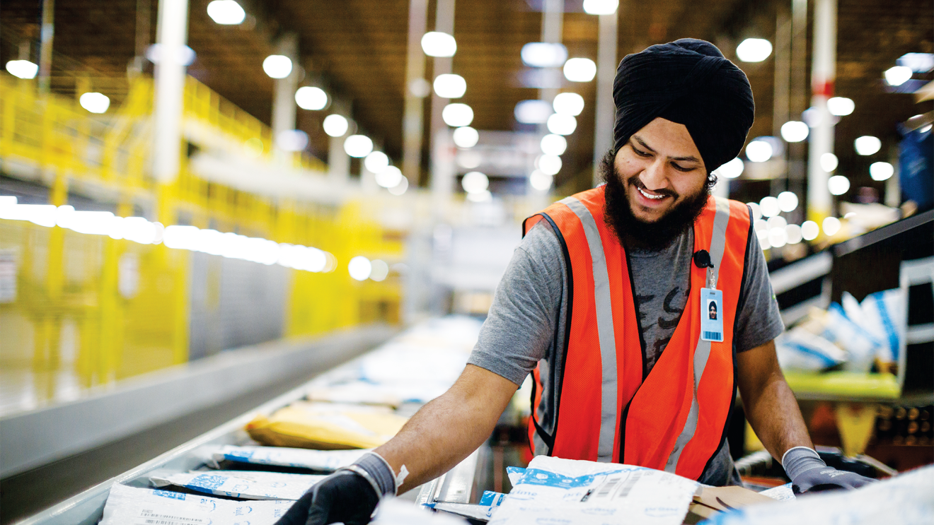 A man, wearing a dastaar (or turban) in an Amazon fulfillment center (warehouse). He is moving packages from a conveyor belt to a large cart to be shipped.