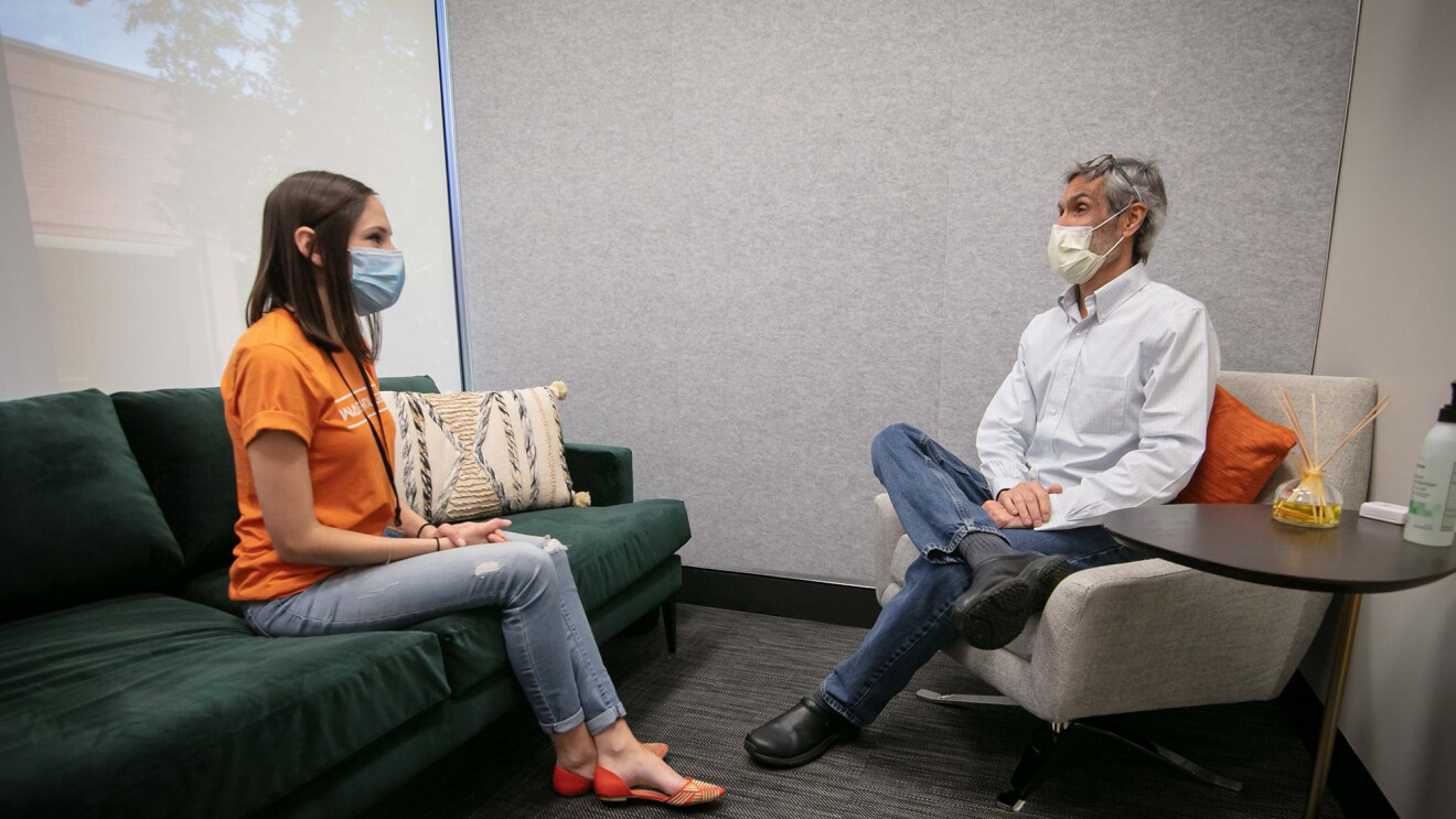 A man and a woman sit in a clinic setting, wearing masks, while speaking.