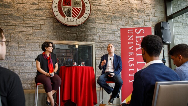 A woman, Roshanak Roshandel sits on a raised chair, next to a man, Andy Jassy, as they lead a fireside chat at Seattle University.