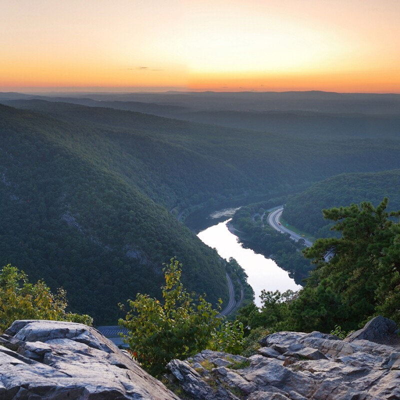 A view of the Appalacian mountains in Pennsylvania overlooking mountains, river, vegetation, in front of a sunset.