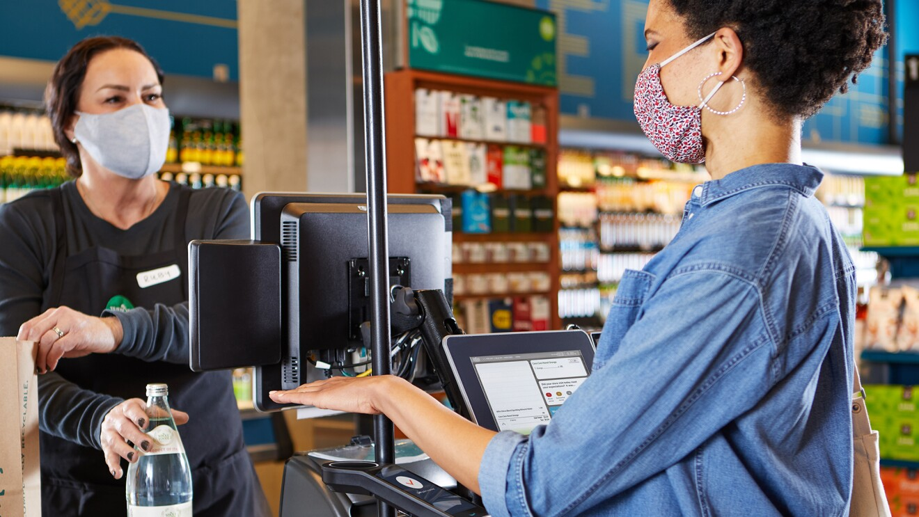 A woman wearing a mask purchases items at a grocery store while an cashier wearing a mask stands behind glass. They are using touchless technology to check out.