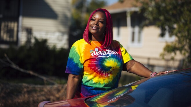 Auhzha Wright stands outside her car wearing a tie-dye shirt with the Amazon logo emblazoned across the chest.
