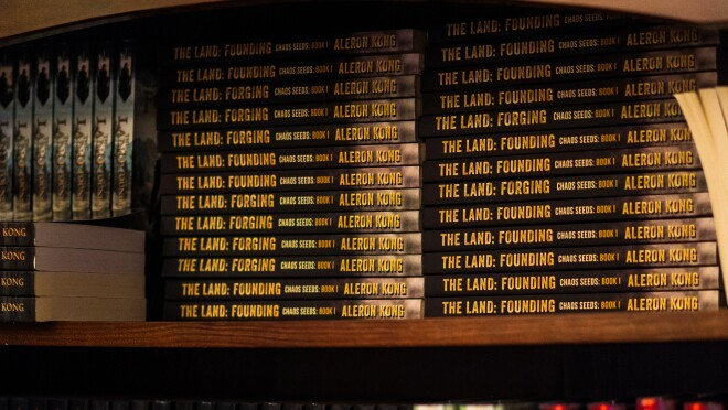 A wood bookcase holds dozens of books bearing the name of author Aleron Kong.
