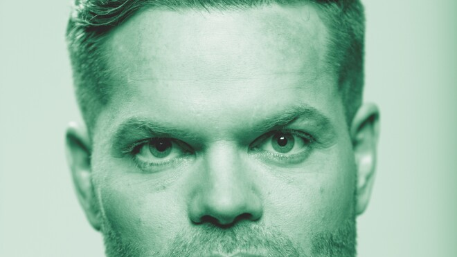"""Wes Chatham, from the Amazon Originals series """"The Expanse"""" poses for a photo. The image has been treated with a green filter."""