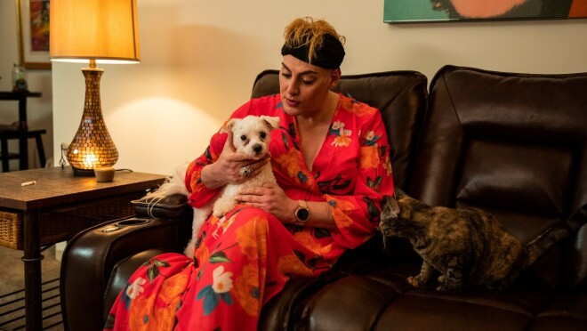 An image of a woman in a pink, floral robe relaxing on her couch with a small white dog and a brown and gold cat.