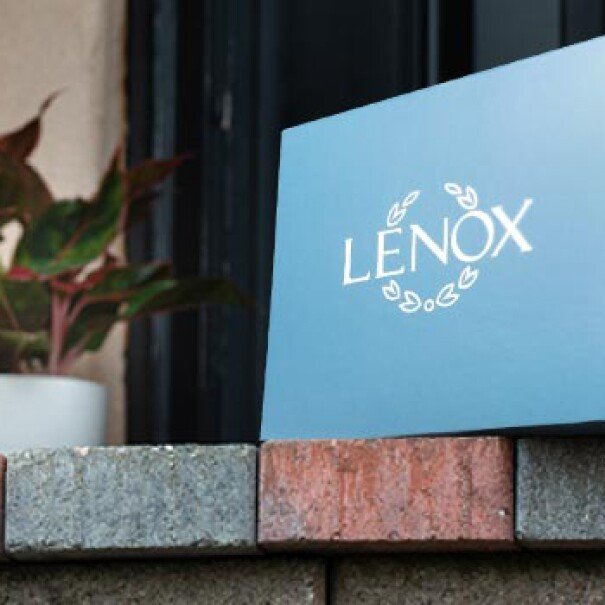 A Lenox glassware box sits on a brick doorstep.