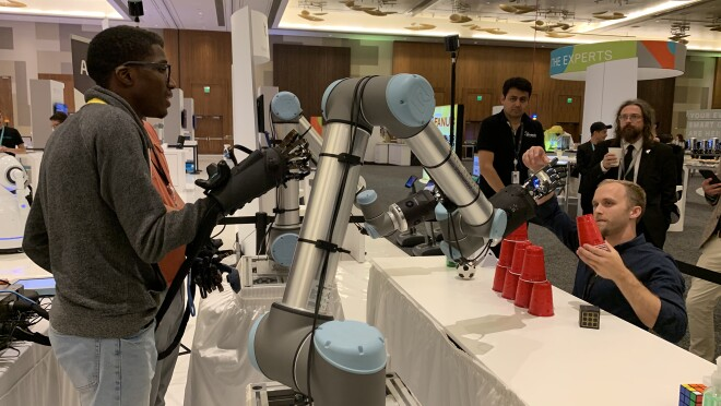 A teen, Leo Jean Baptiste, wears robotic-control gloves and controls a pair of robotic arms with his motions.